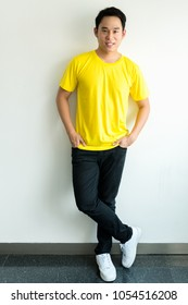 Young Asian man in a blank yellow t-shirt on wall white background.