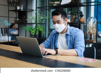 Young Asian Man in blue shirt with face mask working with laptop in coffee shop cafe smile and happy face