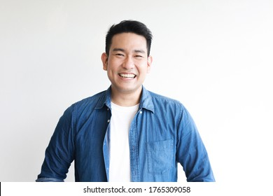 Young Asian man in blue shirt smile and happy face on white background