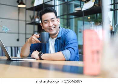 Young Asian Man in blue shirt working with laptop in coffee shop cafe smile and happy face
