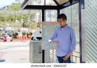 A young Asian man at a bus stop checking his watch as he waits