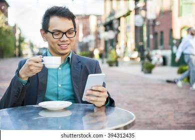 Young asian man in business casual attire sitting and smiling in relaxing outdoor cafe drinking cup of coffee while using mobile phone