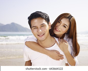 young asian man carrying girlfriend or wife on back on beach.