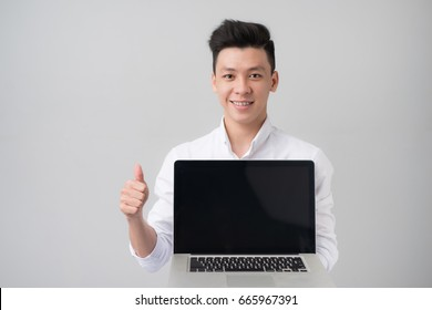 Young asian man in casual clothes holding and showing screen of laptop