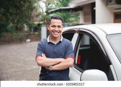 young asian man crossed arm standing in front of his car. taxi driver