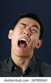 Young Asian man crying and looking upward