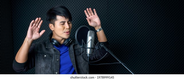 Young asian man dance, swaying, and lifting his arms rhythmically while singing in front of black soundproofing wall. Musician producing music in professional recording studio.