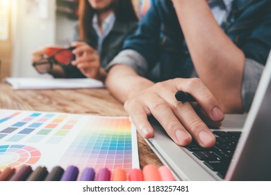Young asian man designer using graphics tablet while working with computer at studio or office,Graphic design and color swatches and pens on a desk warm colours sun light.