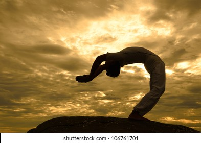 young Asian man doing yoga on the beach