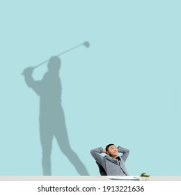 Young asian man dreaming about future in big sport during his work in office. Becoming a legend. Shadow, silhouette of professional golf player on the wall. Inspiration, aspiration. Copyspace.