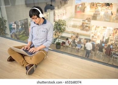 Young Asian man dressed in casual style working with his laptop while listening to music. Digital nomad working in co working space, modern IT lifestyle with work life balance concept.