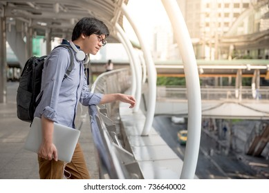 Young Asian man dressed in casual style looking around the street and holding laptop computer in the city, modern IT lifestyle with work life balance concept