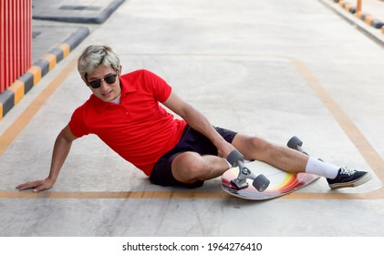 Young asian man dressed in a red T-shirt and black shorts caught his ankle due to a skateboarding accident. He lifted himself with one hand from the ground after the crash.