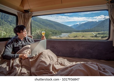 Young Asian man drinking beer and working with laptop computer on the bed in camper van with snow mountain scenic view through the window, digital nomad concept