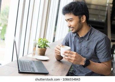 Young Asian man drinking coffee and working laptop computer in coffee cafe