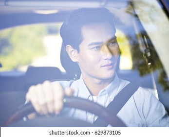 young asian man driving a vehicle, looking at scenery,  seen through the windshield glass.