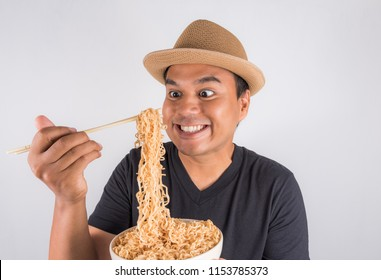 Young asian man eating noodles.