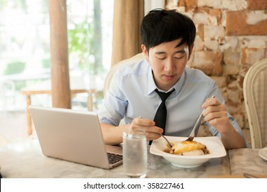 Young Asian man eating and working with his laptop in restaurant
