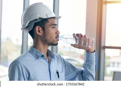 Young asian man engineer drinking the water.