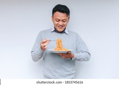 Young Asian man enjoy noodles. Eating lunch concept.