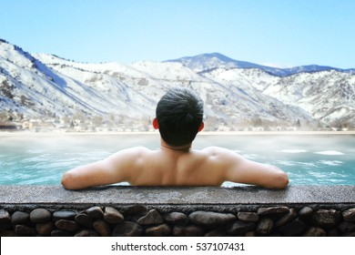 Young asian man enjoying outdoor bathing with scenery of mountains covered with snow.