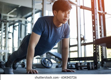 Young Asian man exercising in the fitness gym with flare light