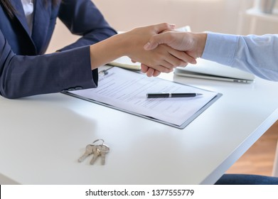 Young Asian man feeling happy after finish buying or rental real estate with agent and shaking hand after sign contract.