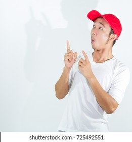 Young Asian man feels shock and surprised gesture keeping mouth wide open with overly face expression, looking shocked