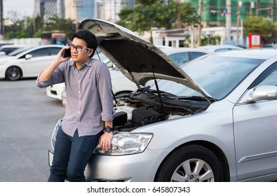 Young asian man has Broken Down car and calling for help