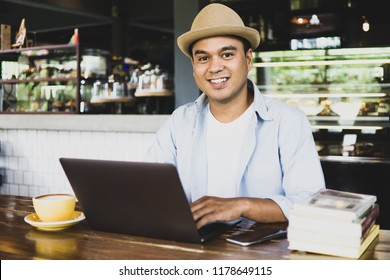 Young asian man with hat using laptop at cafe. A man working on laptop