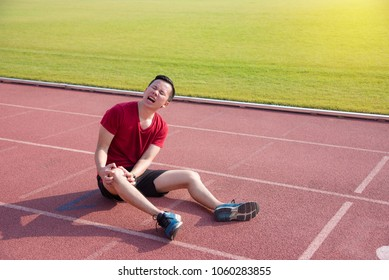 Young asian man having pain at his knee after falling between running