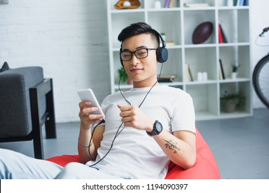 young asian man in headphones using smartphone while sitting in bean bag chair at home