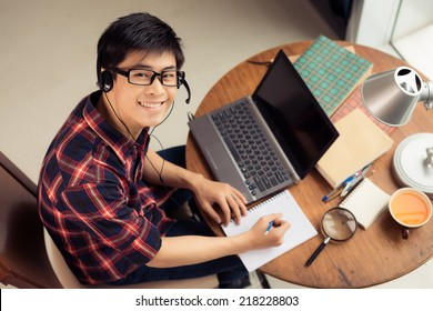 Young Asian man in a headset working on laptop and making notes, view from above