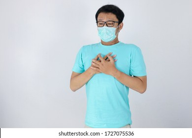 Young asian man with Heart attack or cold flu feeling breathless. He wears a surgical mask and also feels tightness of chest during quarantine life at home. Corona virus outbreak.