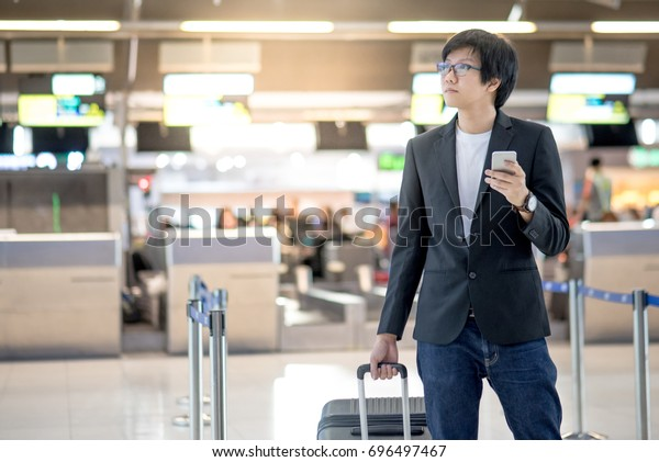 Young asian man with his suitcase luggage using smartphone while waiting for airline flight in the international airport terminal, business travel and online check in concepts