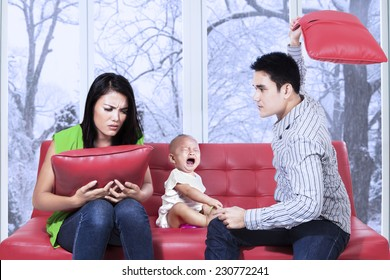 Young asian man hitting his wife near their child and make the child crying
