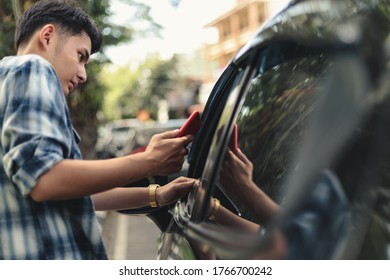 Young Asian man holding cell phone and hailing taxi.