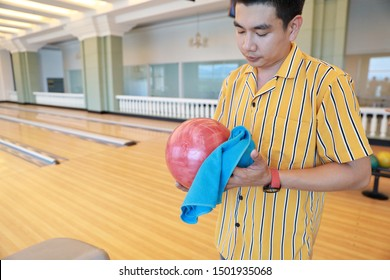 young asian man holding and cleaning bowling ball in sport club