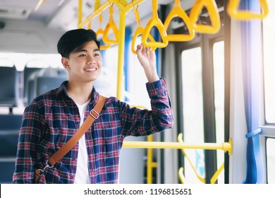 Young asian man holding handle on the public bus.