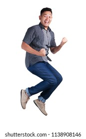 Young Asian man jumping and shows winnig gesture. Isolated on white. Full body portrait