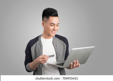 Young asian man with laptop and credit card in studio isolated gray background