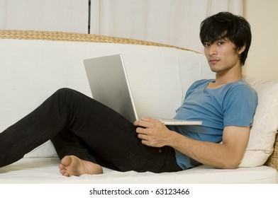 Young Asian man laying on sofa and using computer