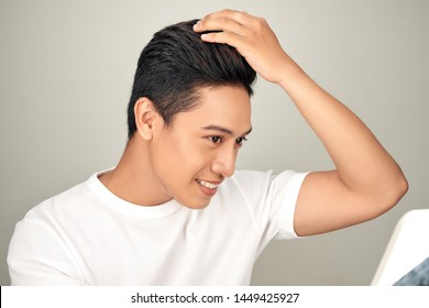 Young Asian man is lokking in mirror and touching his hair on white background