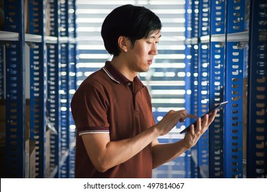 Young Asian man looking up on a tablet in inventory stock warehouse - closeup upper body