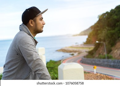 Young Asian man looking to scenic view at khungvimarn, Chalerm Burapha Chonlathit Highway from Noen Nangphaya View Point at Chanthaburi, Thailand.