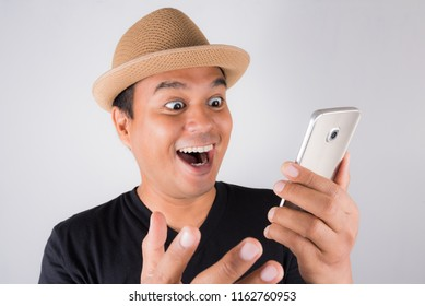 Young asian man looking at smartphone and feels astonished.