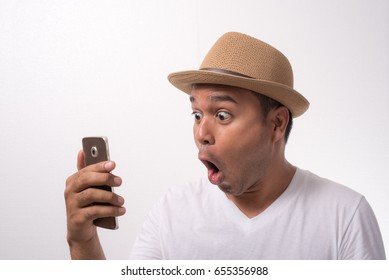 Young asian man looking smartphone and feels shock and surprise with overly face expression.