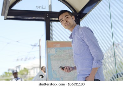 Young Asian man looks out from a bus stop with his phone in hand