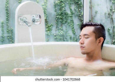 young asian man in  luxury bathtub spa relaxing in hotel