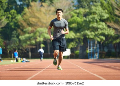 young asian man male athlete running training exercising on track.